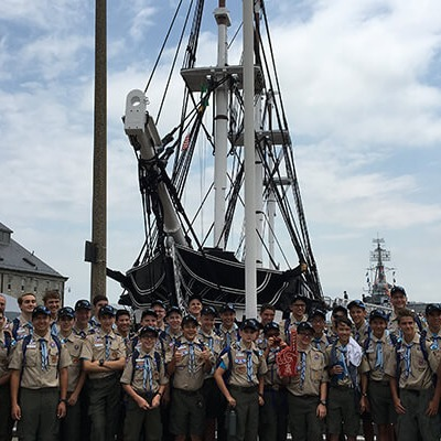 Group of boy scouts posing in front of ship
